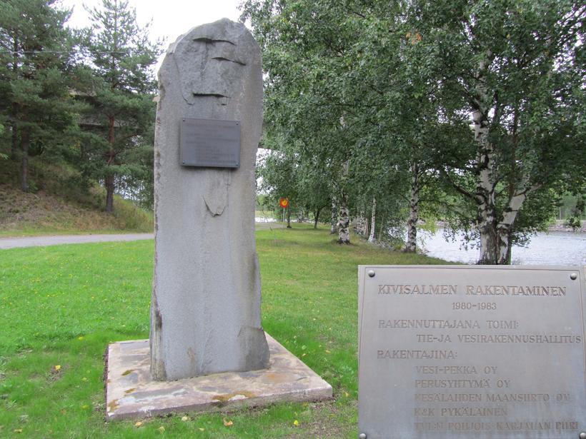 Kanavatyön 1980 - 1983 muistomerkki viimeisteltynä Kivisalmipuistossa lähinnä kanavaa. Suurennettu kuva muistokilvestä liitettynä maisemakuvan alanurkkaan.
