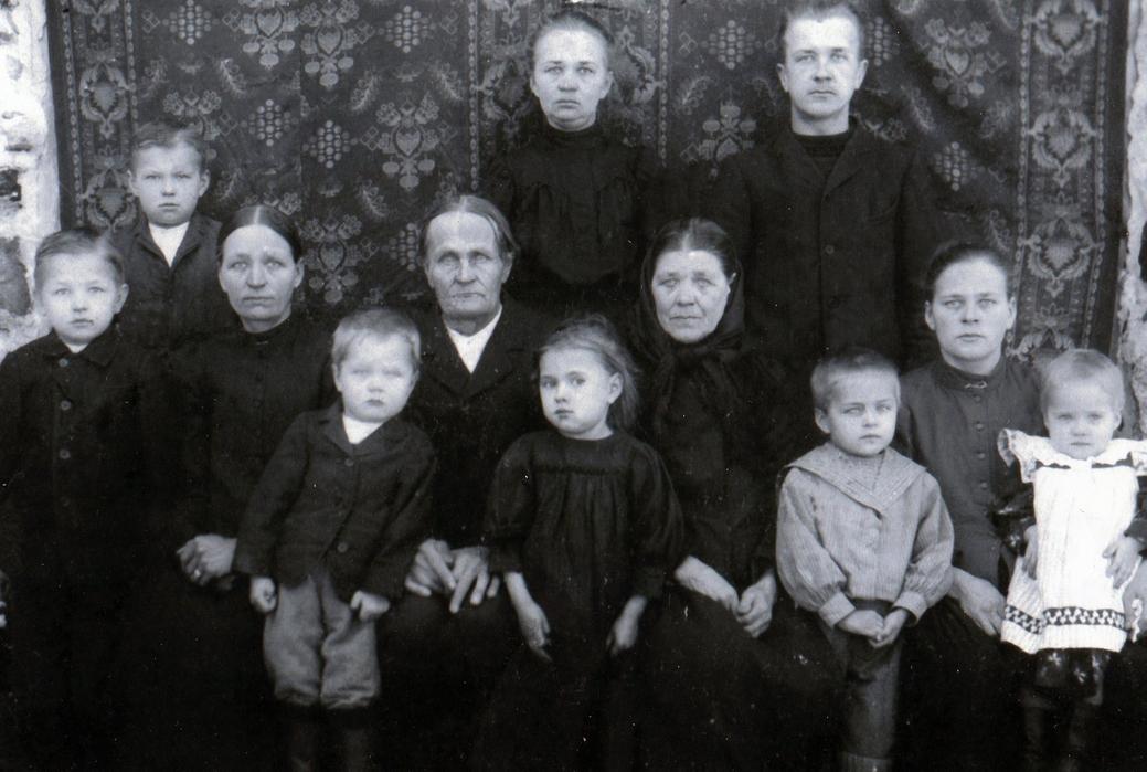 Haapasalmen kirjaston puuhamies Juho Neiglick (s. 1842, talollinen, lautamies) ja hänen puolisonsa Anna Toivanen. Kaikkiaan heille syntyi 13 lasta, joista neljä kuoli pieninä. Kuvassa osa heidän lapsistaan ja lastenlapsistaan. Eturivi vasemmalta: Antti Rouvinen, Aino Rouvinen, Eino Päivinen ja Helli Päivinen. Toinen rivi vasemmalta: Toivo Neiglick (Haapasalo), Eeva Rouvinen os. Neiglick, Juho Neiglick, Anna Toivanen ja Iidä Päivinen os. Neiglick. Takana vasemmalta: Eino Neiglick (Nettamo). Anna Neiglick ja Antti Neiglick. Kuva otettu n. vuonna 1910. Kuvan omistaa Esko Päivinen.